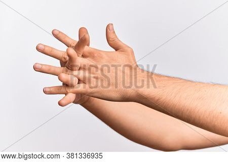 Hand of caucasian young man showing fingers over isolated white background stretching them with fingers intertwined, hands together and fingers interlocked
