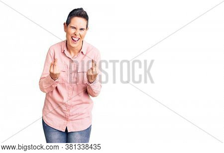 Young woman with short hair wearing casual clothes showing middle finger doing bad expression, provocation and rude attitude. screaming excited