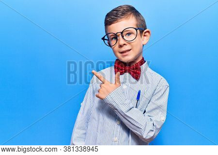 Cute blond kid wearing nerd bow tie and glasses cheerful with a smile of face pointing with hand and finger up to the side with happy and natural expression on face