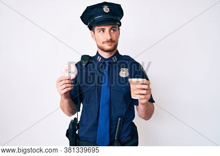 Young caucasian man wearing police uniform holding take away coffee and donut smiling looking to the side and staring away thinking.