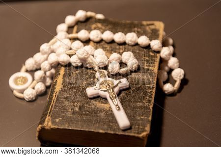 Old Religious Book. Symbols Of Catholicism. Rosary And White Crucifix. Symbol Of Veneration, Which W