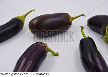Fresh Blue, Purple Eggplants Recently Picked And Arranged On A Matte White Background. Delicious Veg
