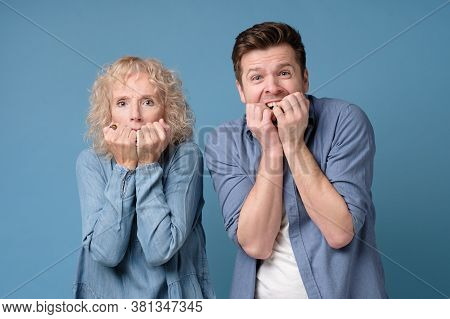 Man And Woman Covering Mouth With Their Hands Being Scared Bitting Nails.