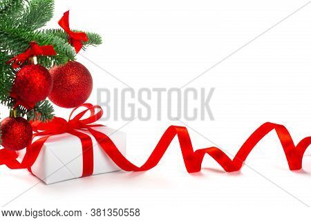 White Holiday Present Gift Box With Red Satin Bow And Curly Ribbon Under Christmas Tree With Baubles