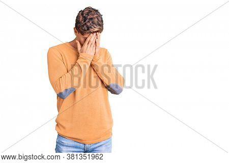Young handsome man wearing casual clothes with sad expression covering face with hands while crying. depression concept.