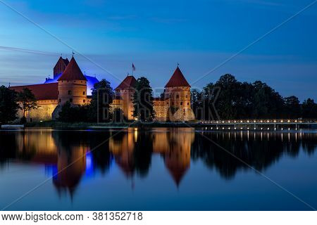 Trakai, Lithuania - July 14, 2020: Trakai Castle After Sunset In The Lake Galve. Trakai Castle Is On