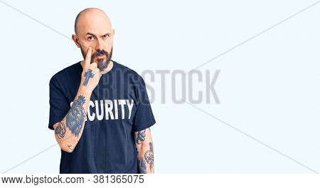 Young handsome man wearing security t shirt pointing to the eye watching you gesture, suspicious expression
