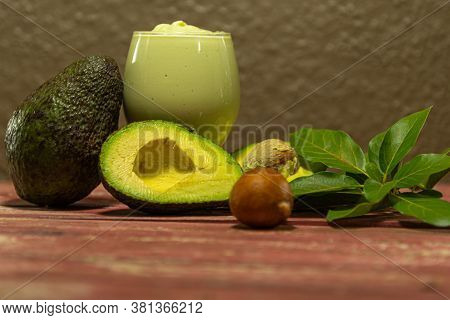 Glass Bowl With Avocado Cream (persea Americana) Between Leaves And Halved Fruits