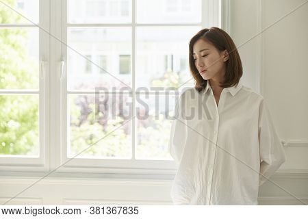 Young Asian Woman Standing By Window At Home Looking Bored And Sad
