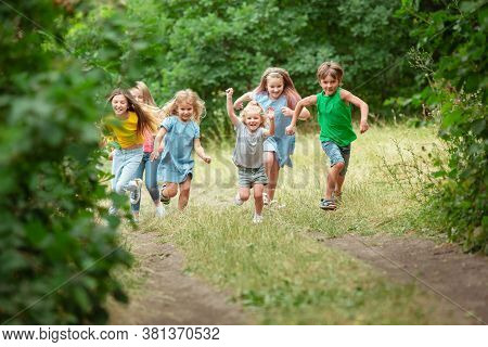 Happiness. Kids, Children Running On Green Forest. Cheerful And Happy Boys And Girs Playing, Laughti