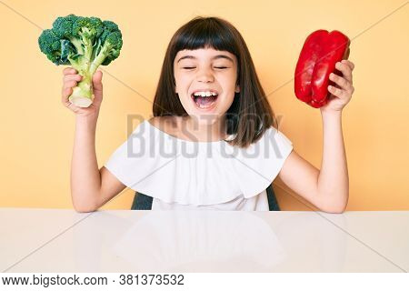 Young little girl with bang holding broccoli and red pepper smiling and laughing hard out loud because funny crazy joke.