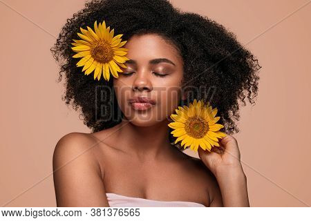 Beautiful Ethnic Woman With Closed Eyes And Clean Skin Putting Fresh Yellow Flowers In Curly Hair Du