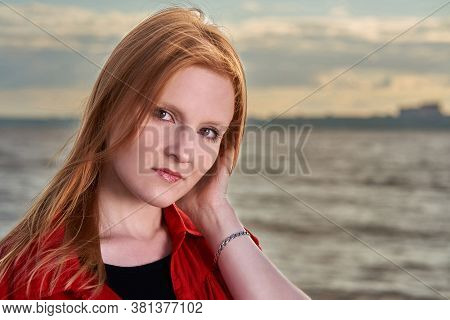 Portrait Of A Red-haired Girl Standing By The Sea.