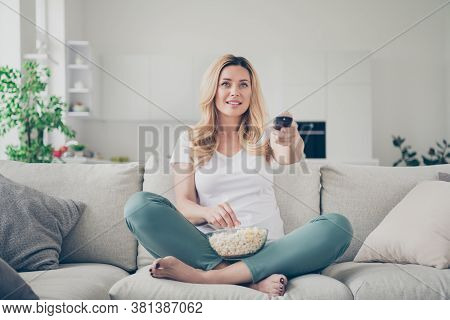 Photo Of Pretty Domestic Beautiful Lady Sit Couch Eat Popcorn Remote Control Change Channel Watch Tv
