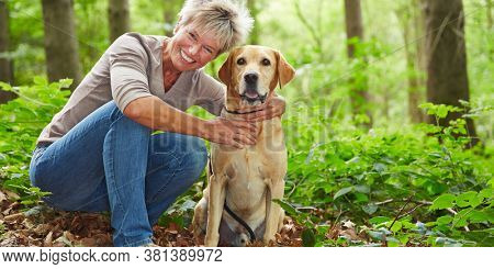 Elderly smiling woman with her Labrador Retriever dog in the forest