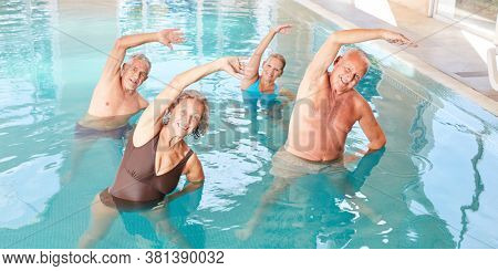Group of seniors exercising their backs at aquafitness course in the pool by a swimming pool