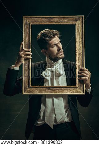 Out Of Time. Young Man In Suit As Dorian Gray Isolated On Dark Green Background. Retro Style, Compar