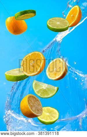 Falling Fresh Mixed Fruits. Slices Of The Lemon, Orange And Lime With Fresh Water In The Air. Flying