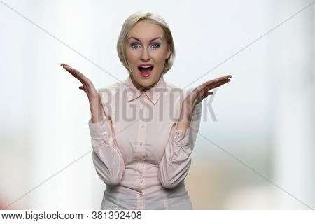 Excited Shocked Business Lady On Blurred Background. Happy Surprised Woman Spreading Her Hands To Th