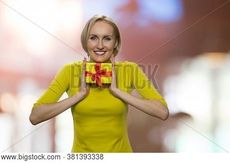 Portrait Of Happy Woman Holding Gift Box With Both Hands. Pretty Smiling Woman With Small Gift Box I