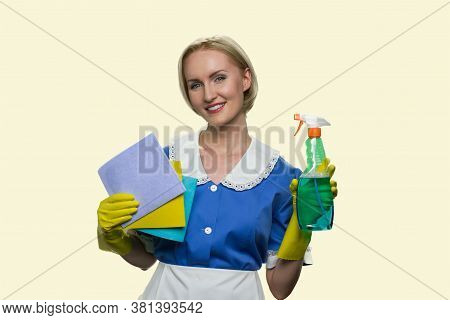 Housekeeper In Uniform Holding Cleaning Supplies. Portrait Of Beautiful Smiling Chambermaid With Rag