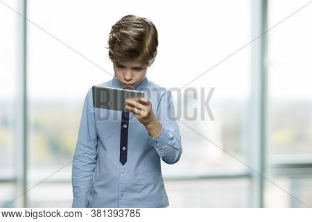 Handsome Caucasian Boy Using Smartphone. Little Boy Looking At Mobile Phone Standing On Blurred Back