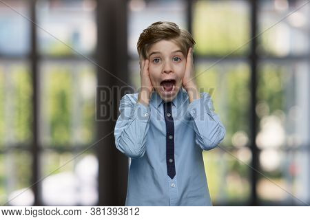 Portrait Of Frightened Child Boy. Shocked Scared Little Boy Screaming Against Blurred Windows Backgr