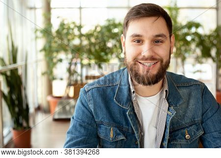 Portrait Smiling Handsome Young Man With Beard In Modern Corporate Environment Near Window. Smart Ma
