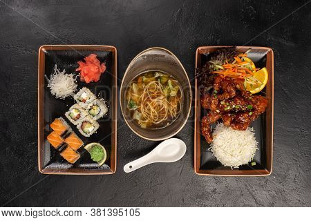 Lunch Menu Of Hot Meat Dish With Rice, Vegetable Soup With Egg Noodles And Sushi Rolls With Salmon,