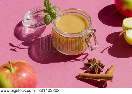 Fresh Organic Homemade Applesauce ,mousse, Sauce In A Glass Jar On A Pink Background. Healthy Natura