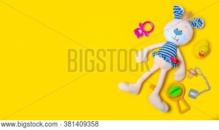 Soft Toy Hare Rabbit, Rattles, Baby Soother On Yellow Background, Top View