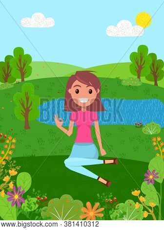 Young Smiling Girl Is Sitting In A Forest Meadow. Woman Shows Okay, On Background Of The River. Mode