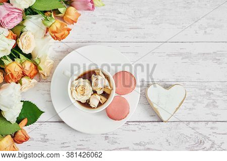 Bouquet Of Roses, Eustomas And Hydrangeas On Table. Cup Of Tea Or Coffee And Macaroons. Greeting Car