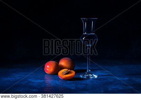 Apricot Brandy In Shot Glass With Fresh Ripe Apricots On Blue Table With Dark Background.