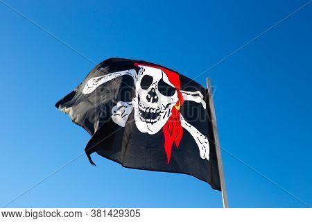 Pirate Flag Flies Against The Blue Sky. Marine Paraphernalia