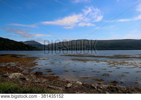 Sea Loch In Scotland With Background Hills At Dusk