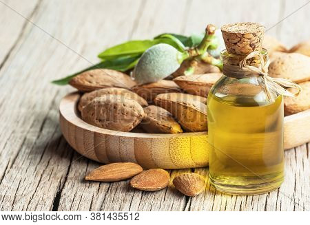 Glass Bottle Of Almond Oil And Almond Nuts, Almonds With Shell In Bamboo Bowl On Wooden Backdrop Wit