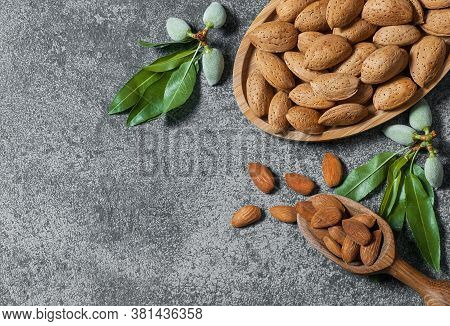 Top View Almond Nuts In Wooden Shovel, Almonds With Shell In Bamboo Bowl On White Table With Green F