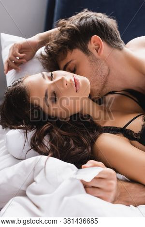 Selective Focus Of Passionate Man Kissing Woman And Holding Condom, Two People