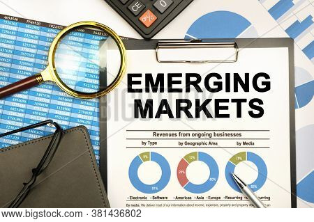 Finance And Business Concept. The Businessman Has On His Desk Graphs With Reports, A Notebook, A Mag