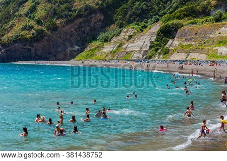 Ribeira Quente, Sao Miguel, Azores, Portugal - August 15, 2020: People swimming in the sea and relaxing on a nice sandy beach Praia do Fogo by the town Ribeira Quente.
