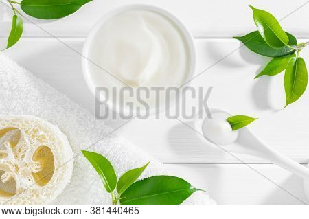 Natural Herbal Cosmetic Cream, Loofah Sponge And Towel On White Wooden Background With Green Leaves.