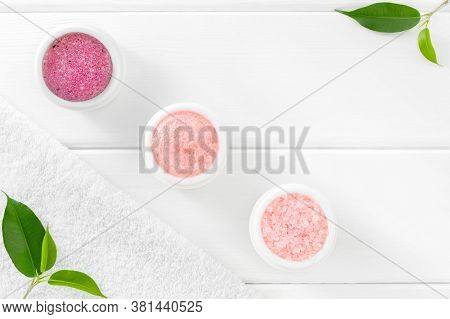 Rose Cosmetic Set For Body Care: Scrub, Exfoliant, Sea Salt And Bath Towel On White Wooden Backgroun