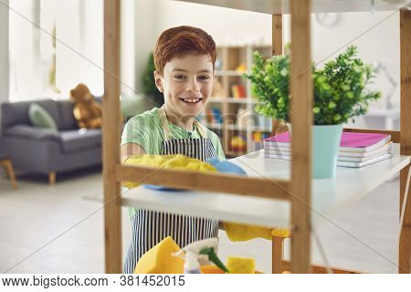Adorable Little Boy In Rubber Gloves Cleaning Shelf With Rag At Home. Cute Kid Helping To Do Domesti