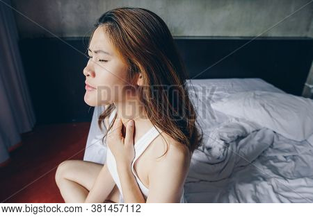 Portrait Of Young Asian Woman Sitting On Bed And Having Painful From Sore Throat. Sore Throats Are C