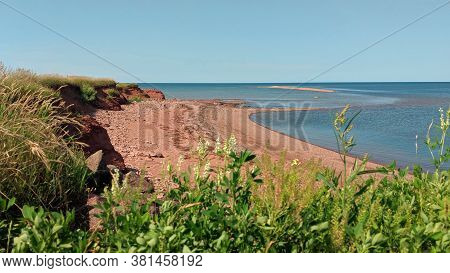 Beautiful Scenery Of North Cape, Pei, Where The Sun Shines Against The Red Sand Beach By The Ocean A