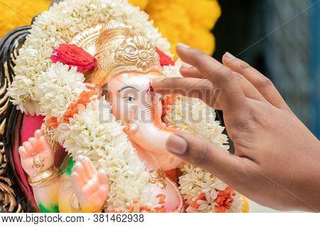 Closeup Of Hands Applying Tilak Or Kumkum To Lord Ganesha During Indian Religious Ganesha Or Vinayak
