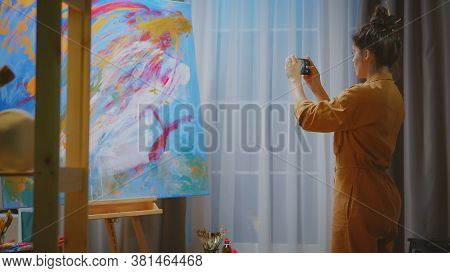 Innovative Woman Painter Taking Photo Of Her Masterpiece In Art Studio.