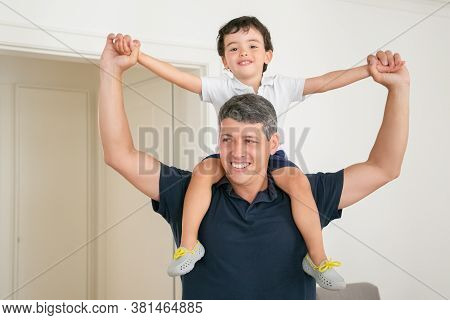 Happy Dad Holding His Son On Shoulders And Spreading Hands. Handsome Caucasian Father In Shirt Playi