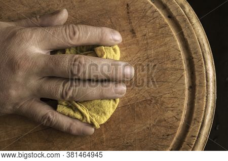 Mature Male Hand Wipes The Cutting Board With Kitchen Rag. Close-up Of Male Hand With Yellow Rag. Ge